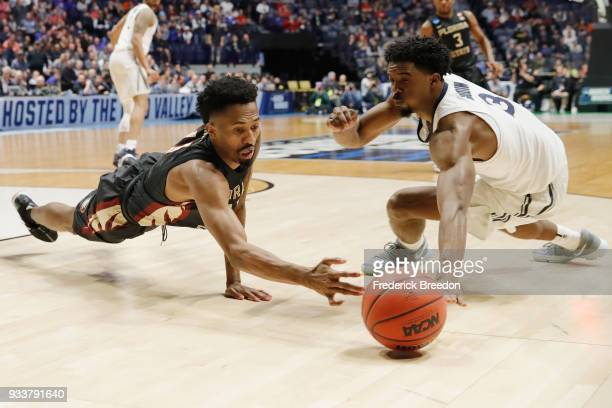 Braian Angola of the Florida State Seminoles dives for a loose ball against Quentin Goodin of the Xavier Musketeers during the second half in the...