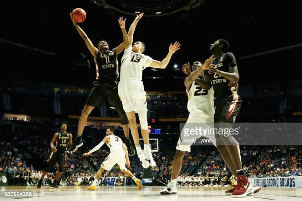 Braian Angola of the Florida State Seminoles shoots a layup over Michael Porter Jr #13 of the Missouri Tigers during the game in the first round of...