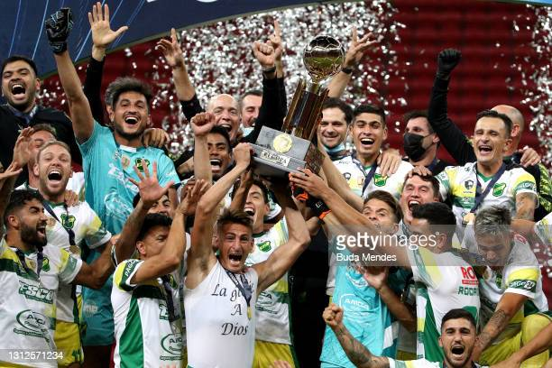 Braian Romero and Ezequiel Unsain of Defensa y Justicia lift the trophy with teammates after winning in a penalty shootout a match between Palmeiras...