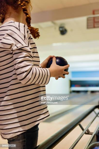 "braided redhead preteen girl playing bowling. - ""martine doucet"" or martinedoucet stock pictures, royalty-free photos & images"
