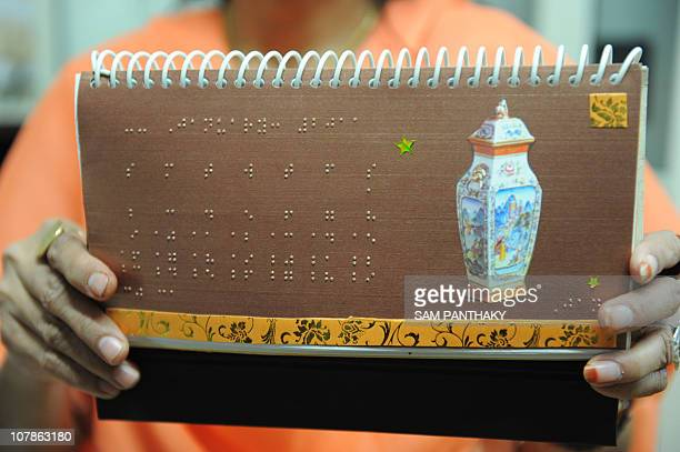 Braille Transcriber Manisha Parikh shows the 2011 Braille Calendar prepared at the Blind People's Association in Ahmedabad on January 4 on the 202nd...