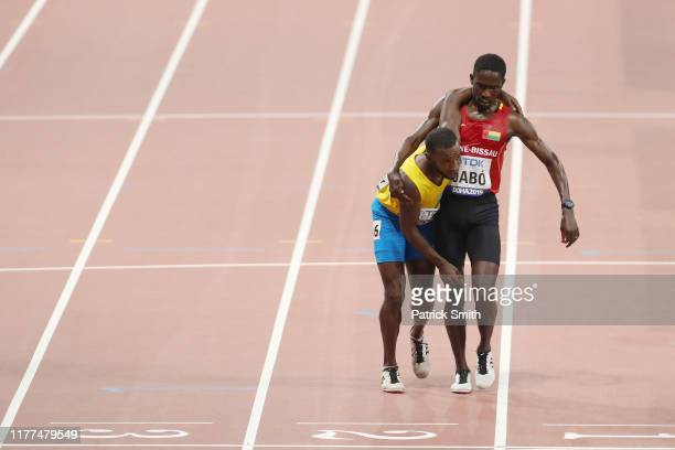 Braima Suncar Dabo of GuineaBissau helps Jonathan Busby of Aruba across the finish line in the Men's 5000 metres heats during day one of 17th IAAF...