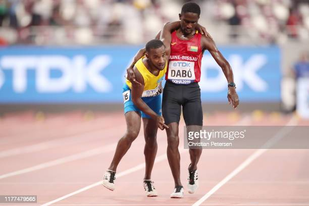 Braima Suncar Dabo of Guinea-Bissau helps Jonathan Busby of Aruba across the finish line in the Men's 5000 metres heats during day one of 17th IAAF...