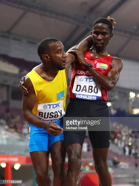 Braima Suncar Dabo of GuineaBissau helps Jonathan Busby of Aruba reach the finish line in the Men's 5000 metres heats during day one of 17th IAAF...