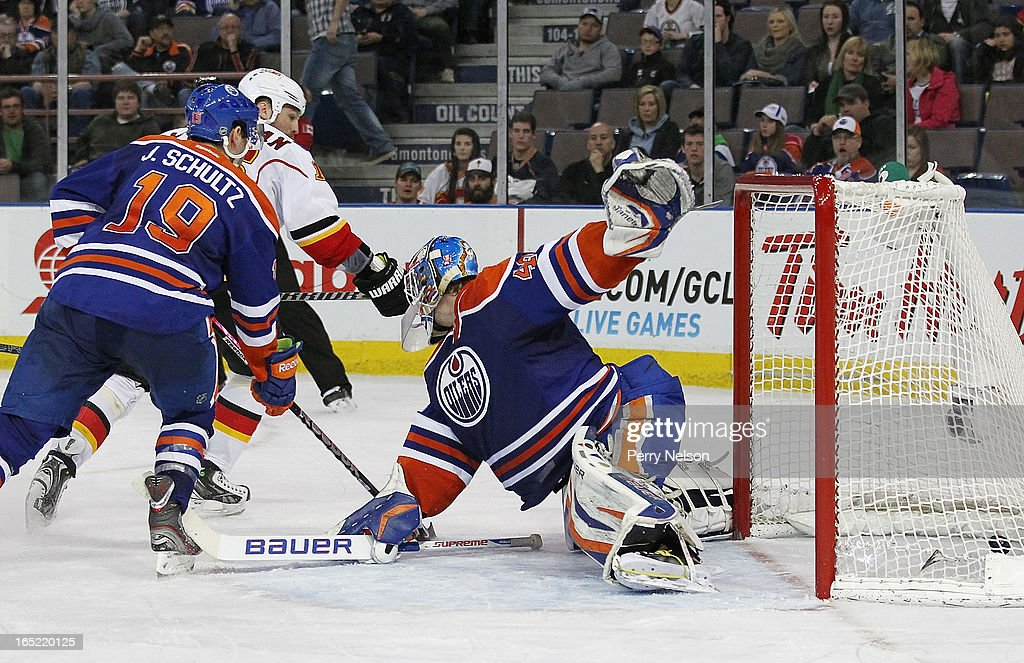 Brain McGrattan #16 of the Calgary Flames beats Justin Schultz #19 and slides the puck past Devan Dubnyk #40 of the Edmotnon Oilers to score the Flames only goal at Rexall Place on April 1, 2013 in Edmonton, Alberta, Canada.