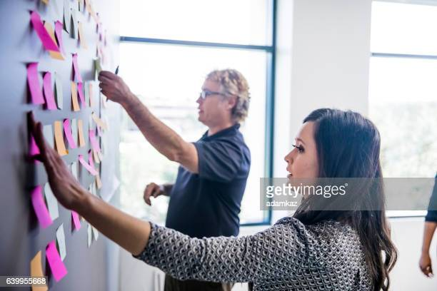 brainstorming with notes on the wall - brainstormen stockfoto's en -beelden