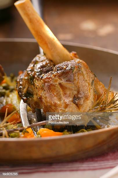 Braised lamb shank with vegetables and rosemary in pan