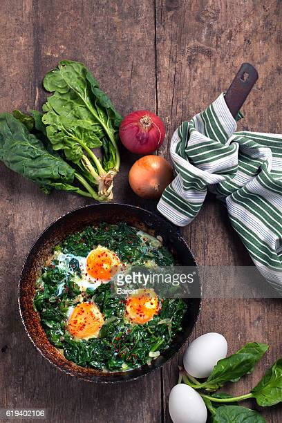 Braised spinach and eggs in an old frying pan