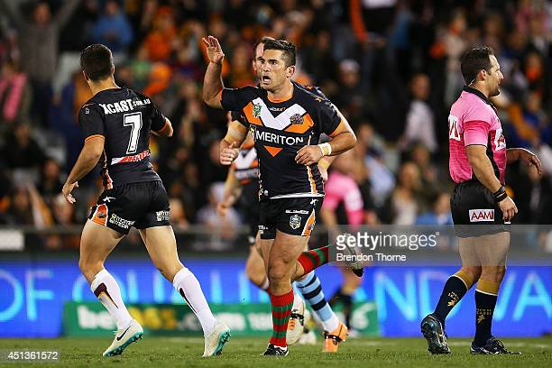 Braith Anasta of the Tigers celebrates with team mate Luke Brooks after kicking a field goal during the round 16 NRL match between the Wests Tigers...