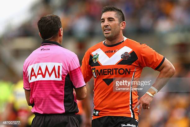 Braith Anasta of the Tigers talks to referee Gerard Sutton during the round 8 NRL match between the Wests Tigers and the Gold Coast Titans at...