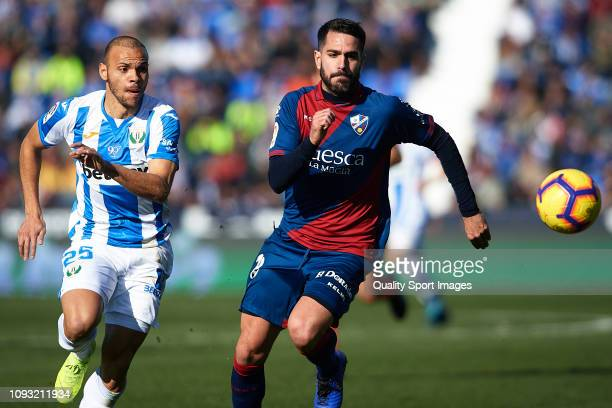 Braithwaite of CD Leganes competes for the ball with Pablo Insua of SD Huesca during the La Liga match between CD Leganes and SD Huesca at Estadio...