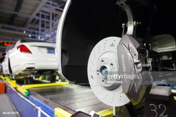 A brake disc hangs from a MercedesBenz SClass automobile as it moves along the production line at the Daimler AG MercedesBenz factory in Sindelfingen...