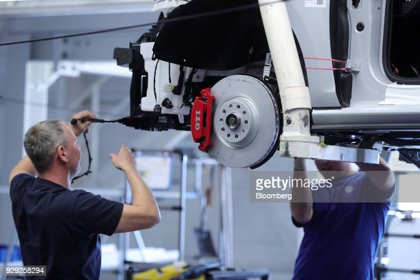 A brake disc sits on a Volkswagen AG Golf GTI automobile as employees assemble the front grille production line at the VW factory in Wolfsburg...