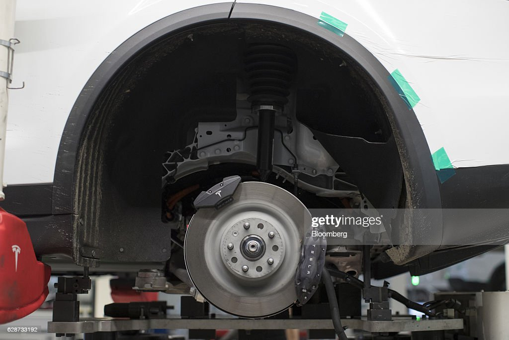 A brake disc sits on the rear axle of a Tesla Model X sports utility vehicle (SUV) during assembly for the European market at the Tesla Motors Inc. factory in Tilburg, Netherlands, on Friday, Dec. 9, 2016. A boom in electric vehicles made by the likes of Tesla could erode as much as 10 percent of global gasoline demand by 2035, according to the oil industry consultant Wood Mackenzie Ltd. Photographer: Jasper Juinen/Bloomberg via Getty Images