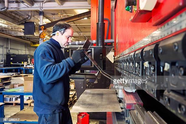 Brake press operator at work in a metalworking factory