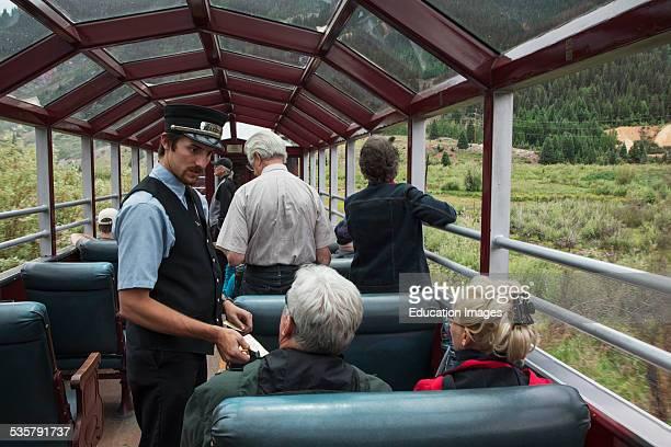 Brakeman takes tickets on Durango and Silverton Narrow Gauge Railroad featuring Steam Engine Train ride, Colorado.
