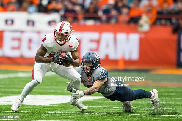 Bra'Lon Cherry of the North Carolina State Wolfpack is brought down by Rodney Williams of the Syracuse Orange during the second quarter on November...