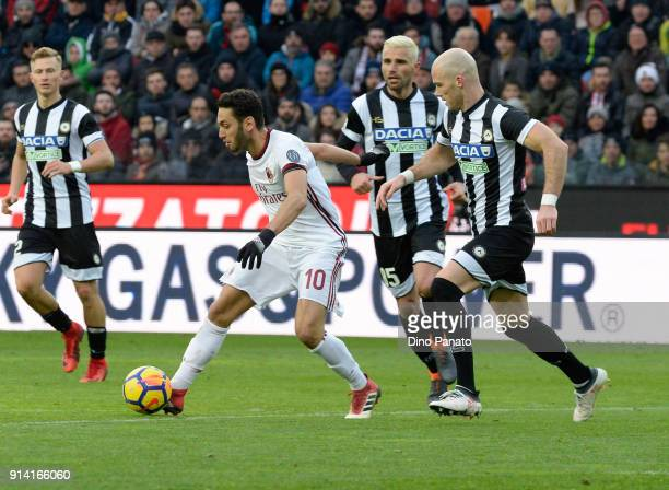 Bram Nuytinc of Udinese competes with Hakan Calhanoglu of AC Milan during the serie A match between Udinese Calcio and AC Milan at Stadio Friuli on...
