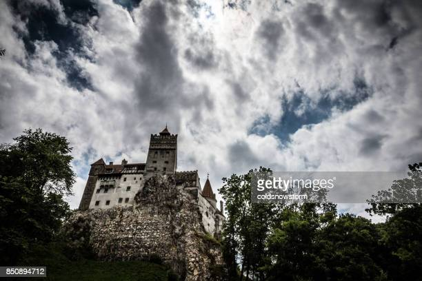 bran (dracula) castle and moody cloudscape, bran, transylvania, romania - count dracula stock photos and pictures
