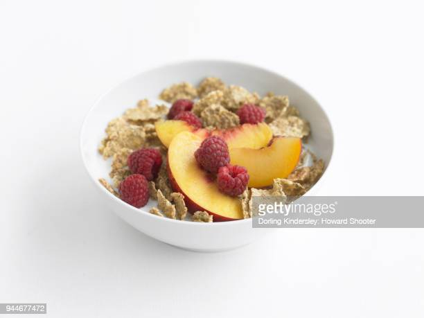 Bran flakes in bowl with milk, peach slices and raspberries