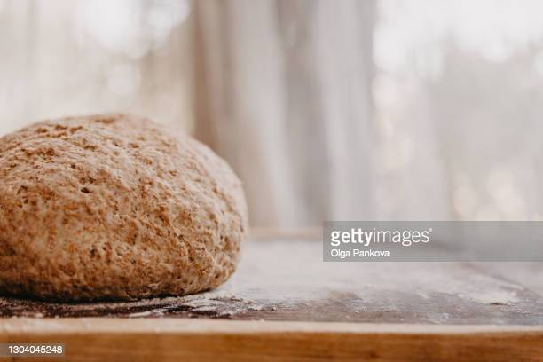 bran wholegrain dough on wooden countertop with flour on background of window. healthy food concept. home cooking.handmade bread. - brown stock pictures, royalty-free photos & images