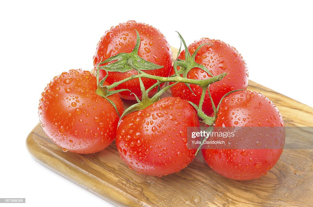 branch of fresh tomatoes on wooden board isolated : Stock Photo