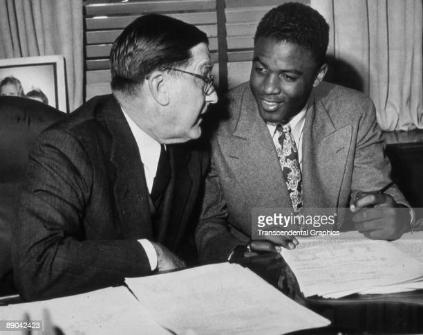 Branch Rickey speaks with Jackie Robinson as he signs his contract with the Brooklyn Dodgers for the 1948 season.