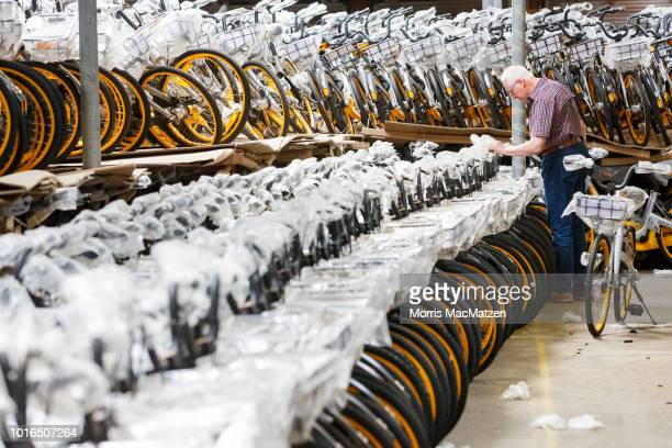 People inspect brand new bicycles left over from the Obike bike sharing business which is for sale at a warehouse where thousands of the bicycles are...