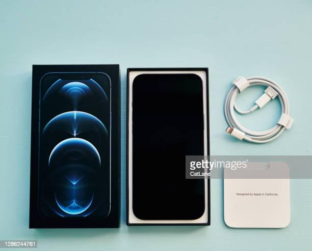 スタジオ設定で充電ケーブルと指示とパシフィックブルーでブランドの新しいiphone 12プロマックス - iphone 12 ストックフォトと画像