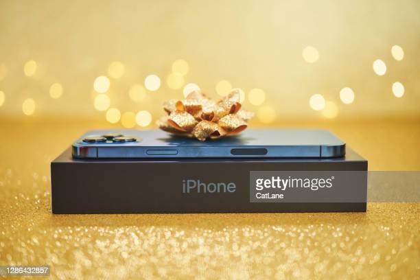 スタジオセッティングでゴールドボウとパシフィックブルーのブランドの新しいiphone 12プロマックス - iphone 12 ストックフォトと画像