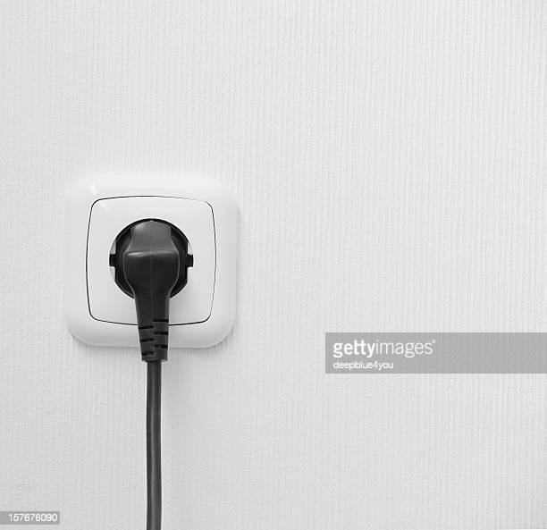 Nuevo en una toma de pared blanco con conector macho
