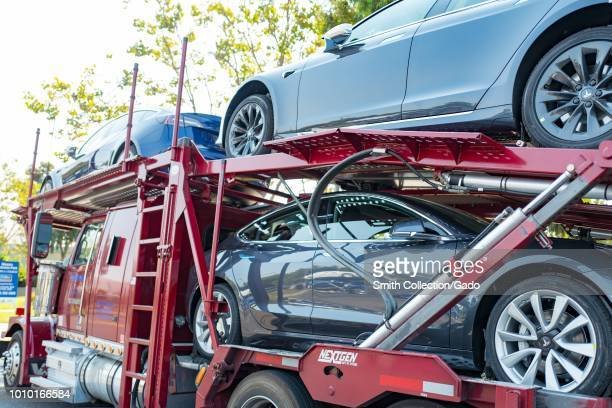 Brand new Tesla motors electric cars including the Tesla Model 3 on a car carrier truck awaiting delivery near the company's headquarters and factory...