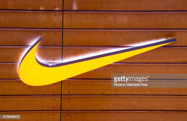 Brand Nike yellow sign or logo attached to a brown wooden wall. Nike, Inc. Is an American multinational corporation that is engaged in the design,...