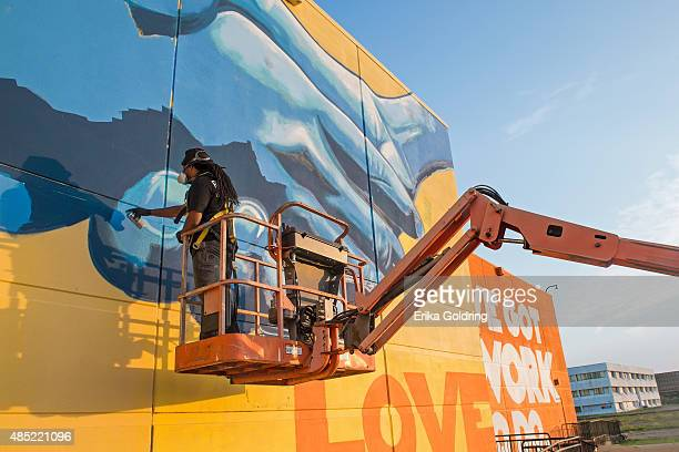 Brandan BMike Odums nears completion of The Wall of Peace mural at The Grand Theater on August 25 2015 in New Orleans Louisiana The timing of the...