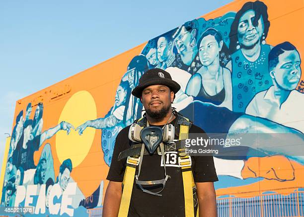 Brandan BMike Odums poses in front of The Wall of Peace mural at The Grand Theater on August 25 2015 in New Orleans Louisiana The timing of the mural...
