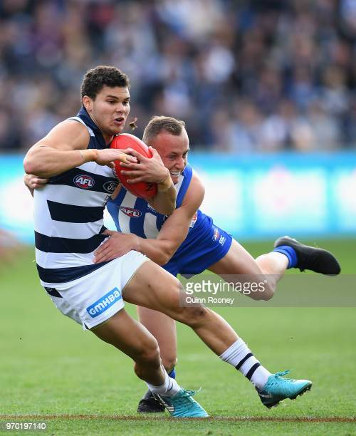 Brandan Parfitt of the Cats is tackled by Billy Hartung of the Kangaroos during the round 12 AFL match between the Geelong Cats and the North...