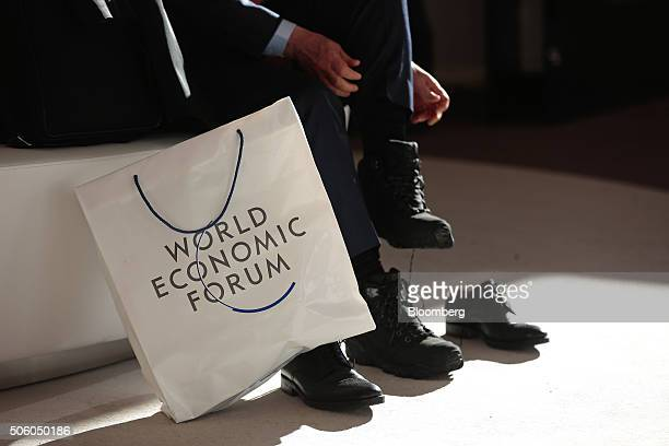 A WEF branded bag sits on the ground as an attendee changes his shoes between sessions during the World Economic Forum in Davos Switzerland on...