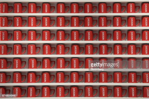 Branded coffee mugs are displayed on a shelf during a media preview of the humanless cafe inside Nestle SA's Nescafe coffee shop in the Harajuku...