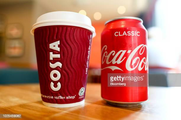 A branded Costa Coffee cup sits next to a can of classic CocaCola manufactured by The CocaCola Co in this arranged photo at a Costa Costa coffee shop...