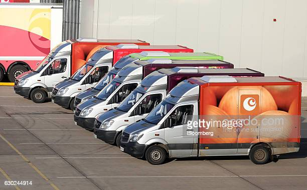 Branded customer delivery vehicles sit ahead of use at the Ocado Group Plc distribution centre in Dordon UK on Friday Dec 16 2016 Ocado provides home...