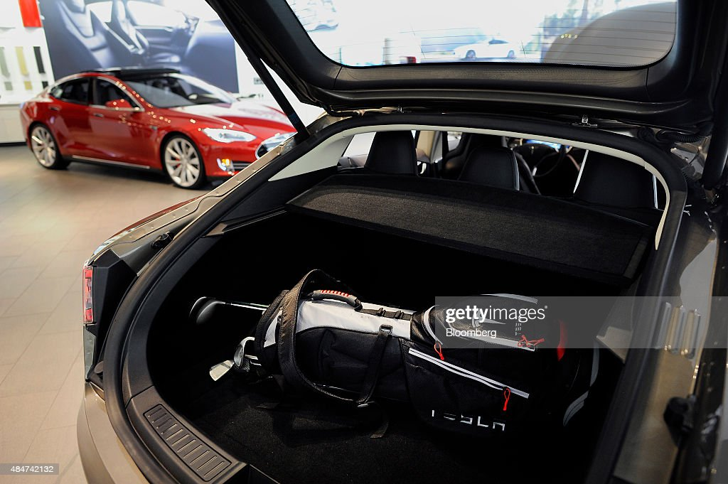 A branded golf bag is displayed in the trunk of a Model S 85