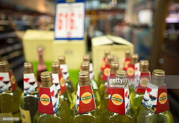 Branded labels sit on the necks of alcohol bottles inside a Metro Cash Carry store the Russia unit of Metro AG in Moscow Russia on Friday Aug 29 2014...