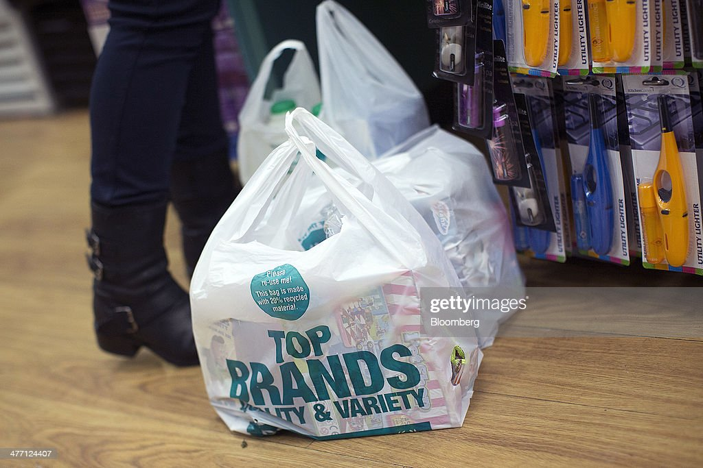 Branded plastic shopping bags containing a customer's goods sit on the shop floor at the check-out desk inside a Poundland discount store, operated by Poundland Group Plc in London, U.K., on Friday, March 7, 2014. Poundland Group Plc has demand for all the shares it is selling in an initial public offering that will value the U.K. discount retailer at as much as 750 million pounds ($1.3 billion), according to terms of the deal. Photographer: Simon Dawson/Bloomberg via Getty Images