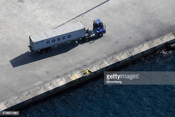A COSCO branded shipping container travels along the dockside on a delivery truck at the COSCO Pacific Ltd terminal area of Piraeus port in Athens...