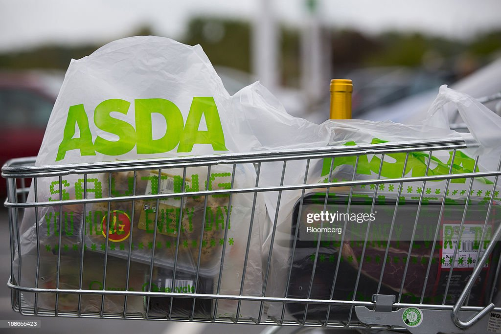 Branded shopping bags containing a customer's purchases sit in a shopping cart outside an Asda supermarket store, operated by Wal-Mart Stores Inc., in the Wandsworth borough of London, U.K., on Monday, May 13, 2013. Asda, the U.K. supermarket chain owned by Wal-Mart Stores Inc., said sales rose 4.5 percent last year and it's investing 700 million pounds ($1 billion) into stores and online operations. Photographer: Jason Alden/Bloomberg via Getty Images