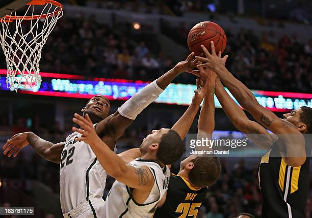 Branden Dawson and Denzel Valentine of the Michigan State Spartans with Eric May and Roy Devyn Marble of the Iowa Hawkeyes reach for the ball during...
