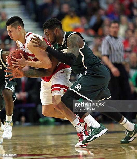 Branden Dawson of the Michigan State Spartans fouls Bronson Koenig of the Wisconsin Badgers as he tries to knock the ball away during the...