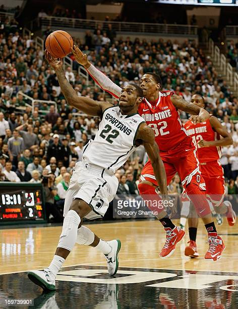 Branden Dawson of the Michigan State Spartans gets caught from behind by Lenzelle Smith Jr #32 of the Ohio State Buckeyes at the Jack Breslin Center...
