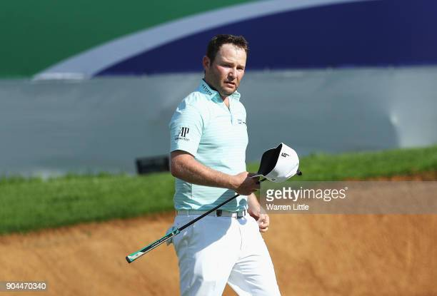 Branden Grace of South Africa acknowledges the crowd as he walks to the 18th green during day three of the BMW South African Open Championship at...