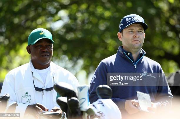 Branden Grace of South Africa and caddie Zacharia Rasego prepares to play on the fourth hole during the first round of the 2018 Masters Tournament at...